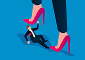istock Feminist concept, male businessman is trampled by female huge heels 1209628723