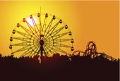 A silhouette of a ferris wheel at sunset.