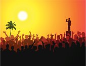 Crowd of people cheering a man with a microphone, with a palm tree in background.