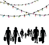 A vector silhouette illustration of a gropup of christmas shoppers carrying shopping bags below strands of christmas lights.