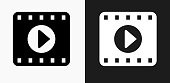 Film Play Icon on Black and White Vector Backgrounds. This vector illustration includes two variations of the icon one in black on a light background on the left and another version in white on a dark background positioned on the right. The vector icon is simple yet elegant and can be used in a variety of ways including website or mobile application icon. This royalty free image is 100% vector based and all design elements can be scaled to any size.
