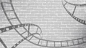 Film strip on grey brick wall. Background in cinematic style on brick wall. Old cinema abstract background. Cinema Movie Time Concept . Graffiti film reel in 3D isometric style.EPS Vector illustration