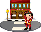 Fireman holding fire extinguisher in front of the firestation