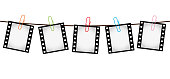 Vector illustration of five empty blank photo 35 mm film slides hanging on a rope with colorful paperclips over white background