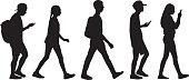 Vector silhouette of five teens walking in line.