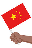 A hand holding flag of China