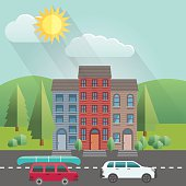 Flat Design Cityscape with mountains in the background.  Two car drive along the road. One has a canoe on its roof.