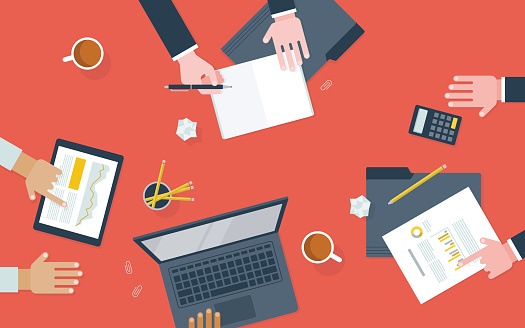 Flat illustration of workers collaborating at desk