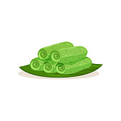Cartoon icon of kuih ketayap on green leaf. Traditional Malaysian dessert. Sweet food. Tasty snack. Asian cuisine theme. Graphic element for cafe menu. Flat vector design isolated on white background.