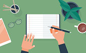 istock Flat vector illustration of person writing in notebook at desk 1298393844