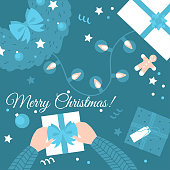 Flat Wrapping gifts. Top view of present boxes and fir wreath on a table with hands. Cartoon creative New Year Workshop. Greeting card with text Merry Christmas