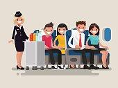 Flight attendant serving drinks to passengers on board of