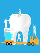 Three dental professionals wearing protective gear floss a giant tooth.