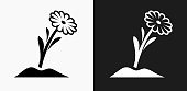 Flower Icon on Black and White Vector Backgrounds. This vector illustration includes two variations of the icon one in black on a light background on the left and another version in white on a dark background positioned on the right. The vector icon is simple yet elegant and can be used in a variety of ways including website or mobile application icon. This royalty free image is 100% vector based and all design elements can be scaled to any size.