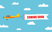 "Flying advertising banner, pulled out by light aircraft with the inscription ""COMING SOON"" - stock vector."