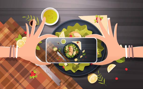 food-bloggerin unter mobile foto der salat aus frischem gemüse mit huhn und soße in schwarz schüssel oberen winkel ansicht smartphone bildschirm sozialnetz aktivität konzept horizontale - fotografieanleitungen stock-grafiken, -clipart, -cartoons und -symbole