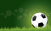 Football on grass field stadium green background  with bokeh.
