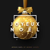 French text Joyeux Noel. Christmas bauble on black background. Xmas gold ball in square frame is on the ribbon with bow. Vector greeting card, poster, banner