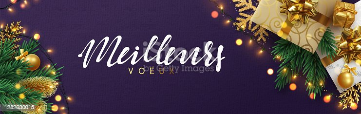 istock French text meilleurs voeux (Translation best wishes) Christmas banner, Xmas sparkling lights garland with gifts box and golden tinsel. 1282630015