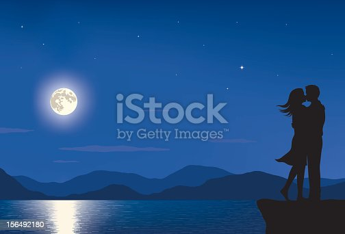 Silhouette of a man and woman kissing in a landscape with full moon and sea at night.