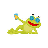 Funny frog in stylish sunglasses lying isolated on white background. Cheerful green toad holding glass of orange juice. Graphic element for greeting card or sticker. Colorful flat vector illustration.