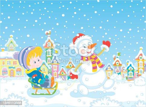 istock Funny snowman sledding a happy little boy 1346110558