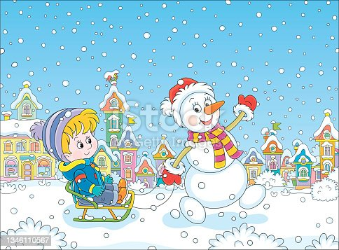 istock Funny snowman sledding a happy little boy 1346110567