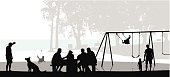 A vector silhouette illustration of people enjoying the park near a beach.  A family gathers at a pinic table, a man plays fetch with his dog, and a father and child walk hand in hand away from a swingset.