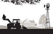 A farmer drives a tractor near his home.