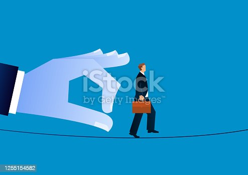istock Giant hand threatens businessman walking a tightrope 1255154582