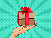 Gift box in hand with red bow and ribbons. Vector illustration.
