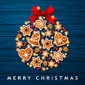 Forming the shape of Christmas bauble by using group of gingerbread cookies, berry fruits, acorns, star shaped decorations and spot lit on the blue colored wood background