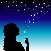 Girl blowing into a dandelion and creating the stars