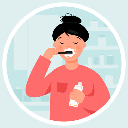 Girl brushing her teeth in the bathroom. Routine hygiene.