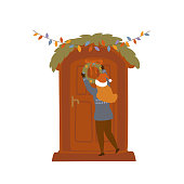 girl decorating entrance house door with christmas wreaths and lights isolated vector illustration scene