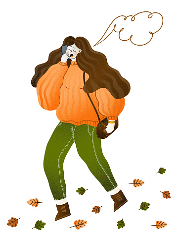 A girl in a cozy sweater walks along an autumn road covered with leaves and speaks on the phone.