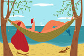 A girl in a swimsuit lies in a hammock on the seashore and reads a book. Summer vacation on the ocean coast.