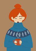 istock Girl in a warm sweater drinks a hot drink. Redhead girl with freckles in a huge cozy sweater holding a cup of hot chocolate. 1281537221