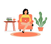 istock A girl sits in a chair and works on a laptop. Home Office. 1227596320