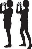 Vector silhouettes of a girl taking photgraphs with her smart phone.