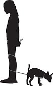 Vector silhouette of a young girl holding a leash that is wrapped around her legs with a small dog on the end of it.
