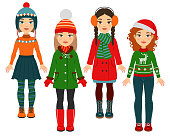Four girls wearing warm clothes isolated on a white background.