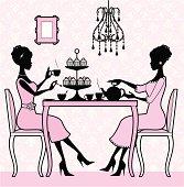 Two elegant women enjoying tea and cakes.