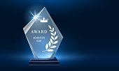 istock Glass trophy award shining with light. Realistic prize for winner in nomination. First place crystal glossy reward 1254275482