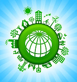 Globe Environment Green Button Background on Blue Sky. The main icon is placed on a round green shiny button in the center of the illustration. Environmental green living lifestyle icons go around the circumference of the button. Green building, man on a bicycle, trees, wind turbine, alternative energy and other environmental conservation symbols complete this illustration. The background has a blue glow effect.