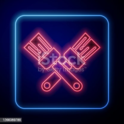 istock Glowing neon Crossed paint brush icon isolated on blue background. Vector Illustration 1266089785
