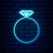 Glowing neon Diamond engagement ring icon isolated on brick wall background. Vector Illustration