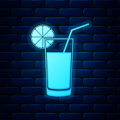 Glowing neon Glass of juice icon isolated on brick wall background. Orange slice and tube for drinking. Healthy organic food. Vector Illustration