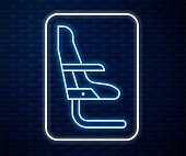 Glowing neon line Airplane seat icon isolated on brick wall background. Vector Illustration