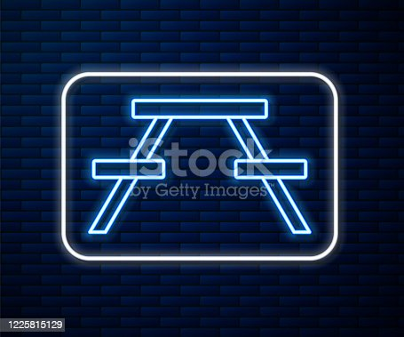 Glowing neon line Picnic table with benches on either side of the table icon isolated on brick wall background. Vector Illustration